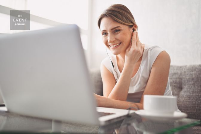 Smiling woman on couch, looking at laptop