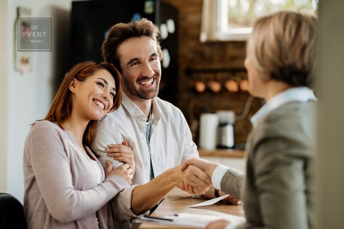 Young happy couple came to an agreement with their insurance agent. Focus is on man shaking hands with the agent.