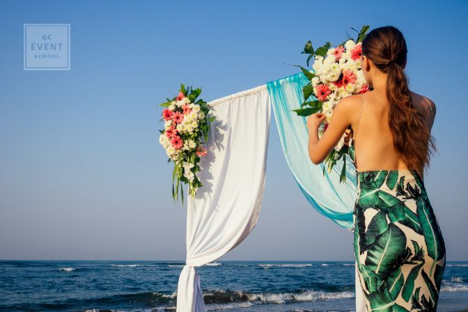 Decorator working with flowers composition for wedding arch on ocean beach