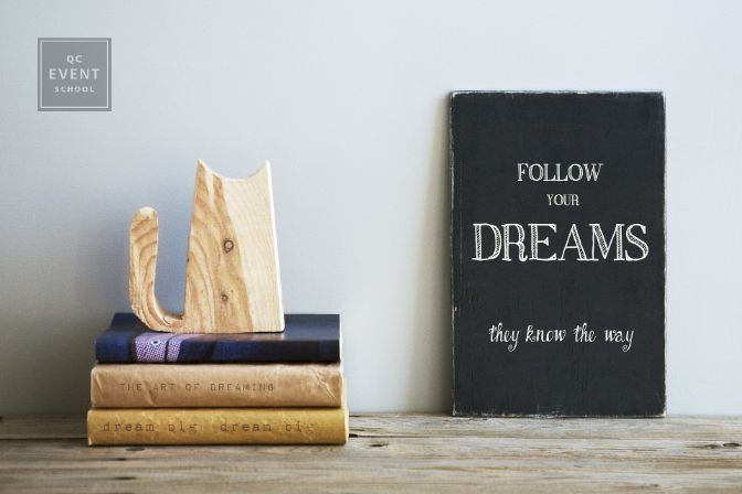 motivational quote FOLLOW YOUR DREAMS on chalkboard with books and wooden cat