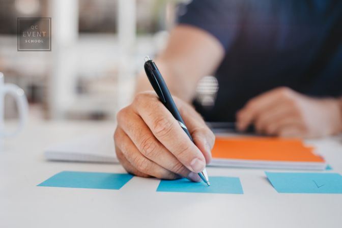 Close up image of business man writing on an adhesive note at table in office, focus on hand and pen.