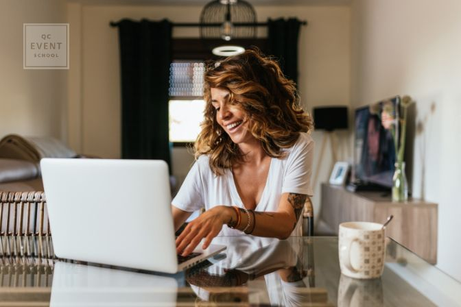 Portrait of a cheerful woman at home with a laptop and a cup of coffee on the table. 30 year old girl connected online to a meeting with friends and family.