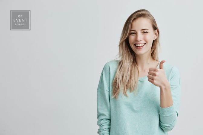 Happy young woman wearing blue long sleeved shirt making thumb up sign and smiling cheerfully, showing her support and respect to someone. Body language. I like that. Good job.
