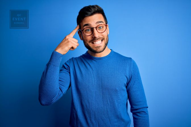 Young handsome man with beard wearing casual sweater and glasses over blue background Smiling pointing to head with one finger, great idea or thought, good memory