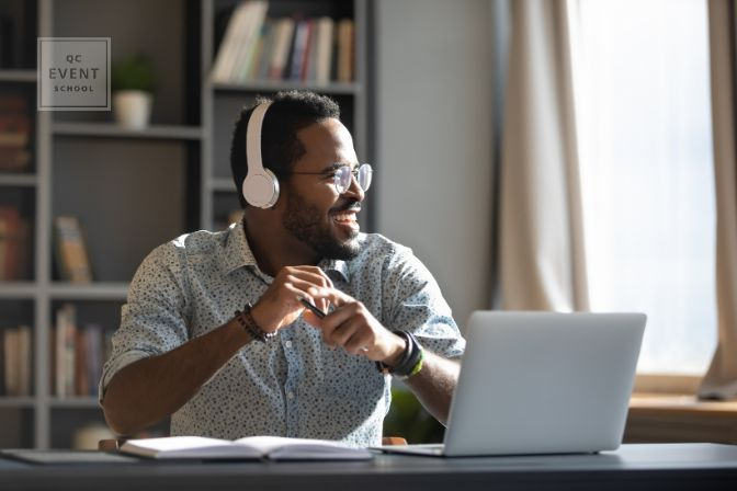 Happy relaxed millennial business man wear wireless headphones look away rest at workplace finished work listening music podcast feel peace of mind concept sit at desk in sunny office