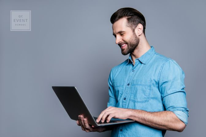 Wedding planner certification article, July 22 2021, in-post image, man smiling and holding laptop