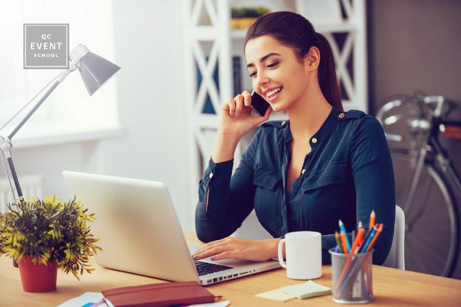 young woman talking on the mobile phone and smiling while sitting at her working place in office and looking at laptop