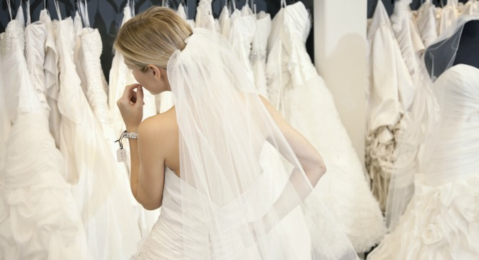 Bride contemplating trying on wedding dresses