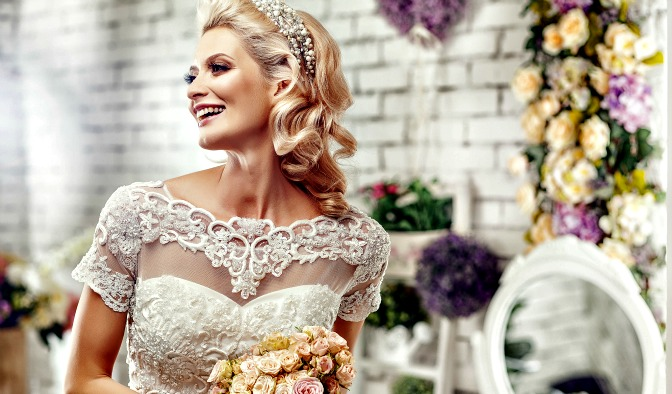 Beautiful bride laughing in dressing room filled with flowers.