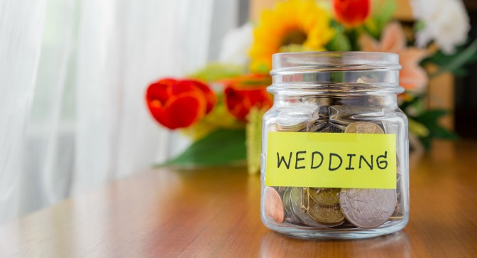 "Jar full of coins marked ""wedding"""