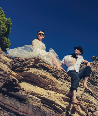Bride and groom wearing sunglasses sitting on a cliff