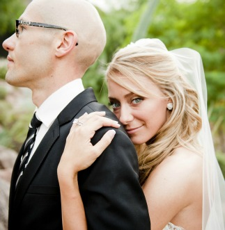 Smiling bride with her arm around her groom's shoulder