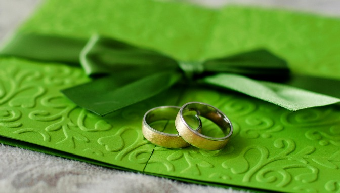 Two wedding rings on a green envelope